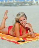 Stunning young blonde woman on beach in bikini Stock Image