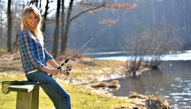 Stunning young blonde woman fishing. Stunning young blonde woman blue flannel shirt sitting on a bench by a pond fishing Royalty Free Stock Photo