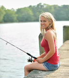 Stunning young blonde woman fishing from pier Stock Image