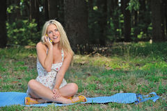 Stunning young blonde woman in sundress with cell phone. Sexy young blonde woman wearing a light sundress lays on a blue blanket in a forest clearing - talking Stock Photos