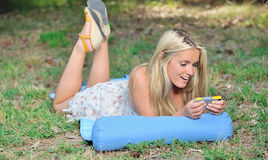 Stunning young blonde woman in sundress with cell phone Royalty Free Stock Photos