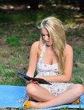 Stunning young blonde woman in sundress - reading Royalty Free Stock Photos