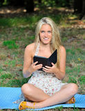 Stunning young blonde woman in sundress reading Stock Photography