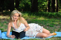 Stunning young blonde woman in sundress reading Royalty Free Stock Photo