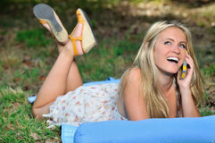 Stunning young blonde woman in sundress - talking on cell phone. Sexy young blonde woman wearing a light sundress lays on a blue blanket in a forest clearing Royalty Free Stock Images