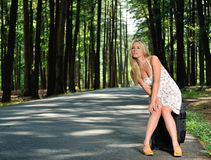 Stunning young blonde woman in sundress - waiting on road Stock Images