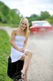 Stunning young blonde woman w/suitcase by road Royalty Free Stock Photo