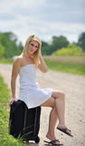 Stunning young blonde woman w/suitcase by road Royalty Free Stock Photography