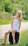 Stunning young blonde woman w/suitcase by road Royalty Free Stock Images