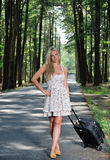 Stunning young blonde woman w/suitcase by road Stock Images