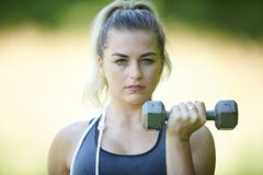 Beautiful blonde female fitness model outside in summer. Stunning young blonde woman working out in summer heat - doing bicep curl - fitness sweat glistening on royalty free stock image