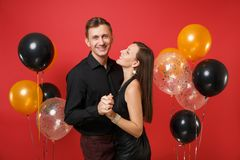 Stunning young couple in black clothes celebrating birthday holiday party isolated on bright red background air balloons royalty free stock photography