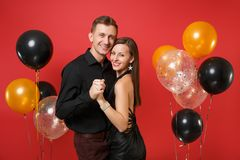 Stunning young couple in black clothes celebrating birthday holiday party isolated on bright red background air balloons royalty free stock photos