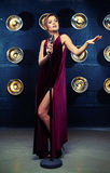 Stunning young female vocalist in shiny black evening dress sing Royalty Free Stock Images