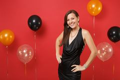 Stunning young girl in little black dress celebrating, stand with arms akimbo on bright red background air balloons. St. Valentine`s, Women`s Day Happy New royalty free stock images