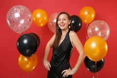Stunning young girl in little black dress celebrating standing with arms akimbo on bright red background air balloons. International Women`s Day, Happy New stock photography