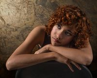 Stunning young mixed race woman leaning on her arms looking up. Stunning young mixed race woman with lovely naturally curly auburn hair leaning on her arms Stock Photography