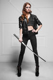 Stunning young woman. In black clothes posing with steel sword royalty free stock image