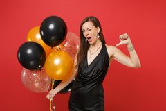 Stunning young woman in black dress celebrating blinking pointing thumb at herself, holding air balloons isolated on red. Background. Women`s Day, Happy New royalty free stock photography