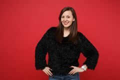 Stunning young woman in black fur sweater standing with arms akimbo on waist isolated on bright red wall background. Studio portrait. People sincere emotions royalty free stock photo