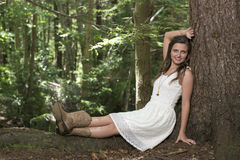 Stunning young woman poses in woods wearing white dress Stock Images