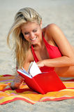 Stunning young woman reading on the beach - bikini Stock Photography