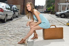 Stunning young woman by road with vintage suitcase Stock Image