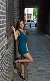 Stunning young woman in romper poses in alley Royalty Free Stock Photo