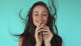 Stunning young woman shakes her hair with her hand, touches her face, dances and whirls against the wind in reverse stock video footage