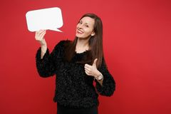 Stunning young woman showing thumb up, holding empty blank Say cloud, speech bubble for promotional content isolated on. Red background. People sincere emotions royalty free stock image