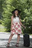 Stunning young woman waits on roadside with suitcase Stock Photo