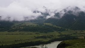 Stunningly beautiful view of the mountain slopes, the valley with bright lush greenery and low-flying clouds. Mountains in fog stock video