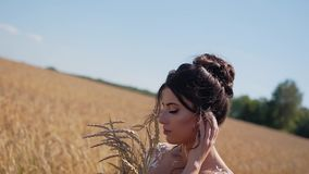 Stunningly beautiful young girl in a classy wheat field. She stands with a bouquet of spikelets in her hands and gently presses th