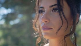 Stunningly beautiful young girl with a thoughtful look in the sunlight. She`s upset about something stock video