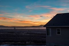 Stunning sunset looking off a house deck beyond the river and mountains Stock Photos