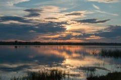 Stunningly härlig solnedgång på ett damm utan en vind Royaltyfri Fotografi