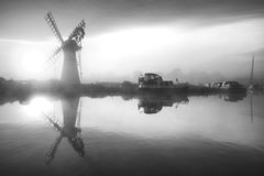 Stunnnig landscape of windmill and calm river at sunrise in blac Royalty Free Stock Photography