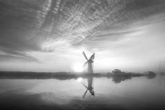 Stunnnig landscape of windmill and river at dawn in black and wh Royalty Free Stock Image