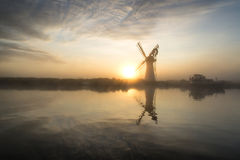 Stunnnig landscape of windmill and river at dawn on Summer morni