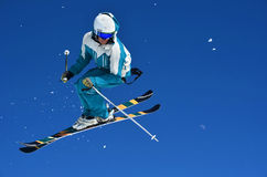 Stunt Jump. VERBIER, SWITZERLAND - MARCH 3: Freestyle performing a high jump against a blue sky trailing snow:  March 3, 2012 in Verbier, Switzerland Stock Images