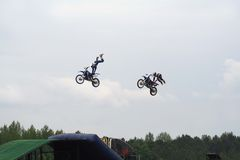 Stunt Motorcycles. Two stunt motorcyclists performing stunts in midair stock photo