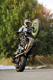 Stunt performer doing motorcycle tricks. Ivano-Frankivsk, Ukraine - 28 August 2015 :Portrait of a male biker showing off tricks on a motorcycle during sunny day stock photography