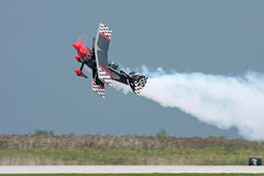 Stunt Plane. A stunt plane flying sideways with a smoke trail Stock Photography