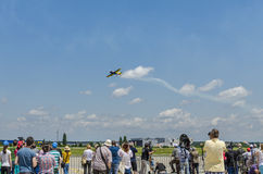 Stunt plane at air show. People watching stunt plane soaring through the air on June 22, 2014 in Bucharest, Romania Royalty Free Stock Images