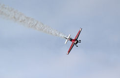 Stunt plane diving with smoke trail. A stunt plane diving towards the camera with a smoke trail behind Stock Image