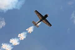 Stunt plane soars in air. Stunt plane leaves a vapor trail in the sky at an air show stock photography