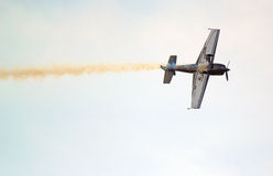 Stunt plane upside down with smoke trail. A stunt plan flying on its side and a smoke trail or plume coming from the back of the aeroplane Stock Photo