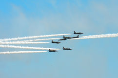 Stunt Planes Daring Maneuvers. A group of five jet planes pass closely by two jet planes headed in the opposite direction during an aerial demonstration at an Royalty Free Stock Images