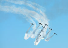 Stunt planes in formation. A group of eight jet planes fly in an arrow formation while completing a complex maneuver, trailing smoke during an airshow Royalty Free Stock Image