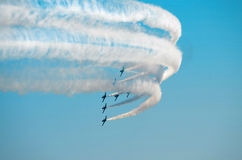 Stunt planes in formation. A group of eight jet planes fly in an arrow formation while completing a complex maneuver, trailing smoke during an airshow Stock Images